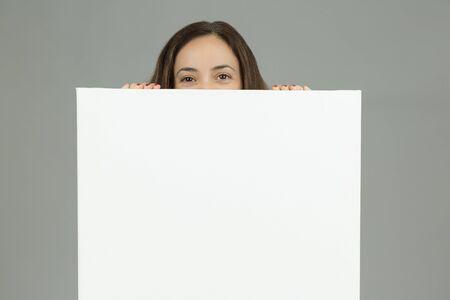 exhibiting: Woman looking behind a blank advertising board
