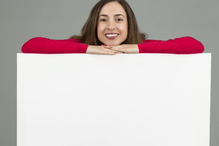 grey background: Smiling woman standing behind an advertising banner on grey background