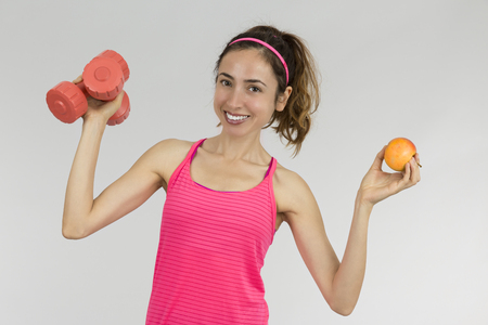 healthy sport: Fit woman showing an apple and dumbbells Stock Photo
