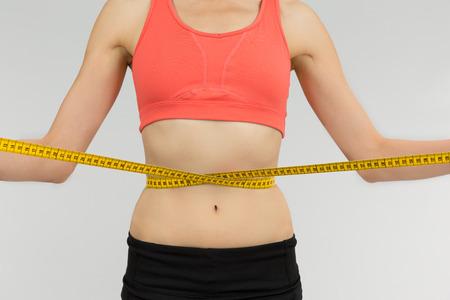 vientre femenino: Mujer de la pérdida de peso con una cinta de medición