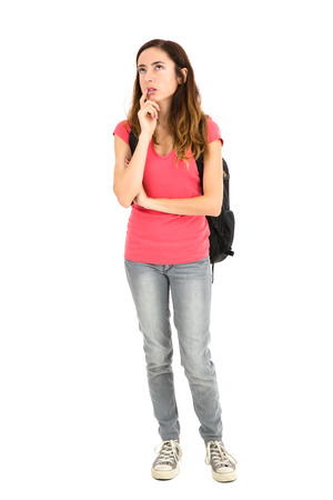 Female student with a backpack thinking and looking up. Isolated on white background. Standard-Bild