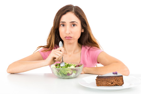 yearning: Weight loss woman eating salad wishing for a piece of cake