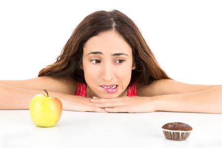 pastel de chocolate: Dieta de la mujer que mira a un muffin y una manzana Foto de archivo