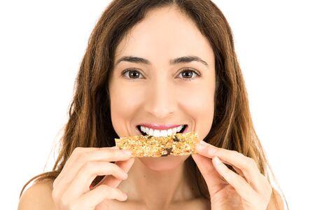 comiendo cereal: Mujer que come la barra de energía