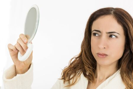 beautycare: Woman looking to herself in the mirror