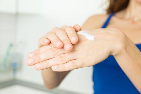 creme: Woman hands applying hand creme