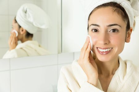 cotton ball: Woman cleaning her face with a cotton ball