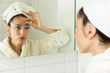 aging face: Woman looking to her wrinkles in the mirror