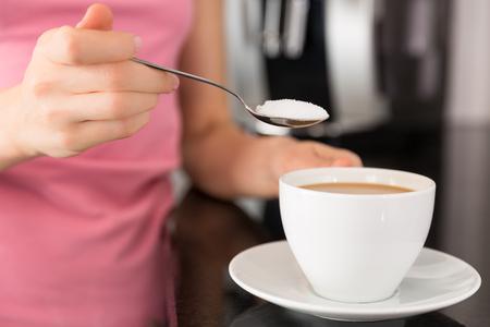 adding: Woman adding sugar to the coffee