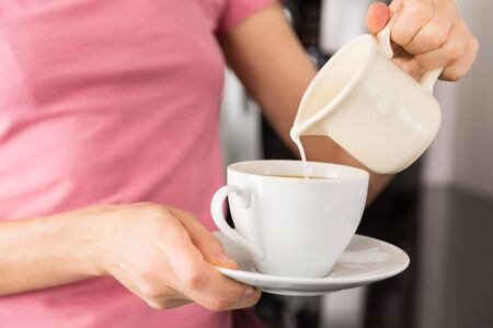 adding: Close up of the hands of woman adding milk to her coffee in the kitchen Stock Photo