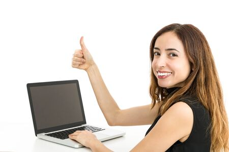 Woman with a laptop giving thumbs up Stock Photo
