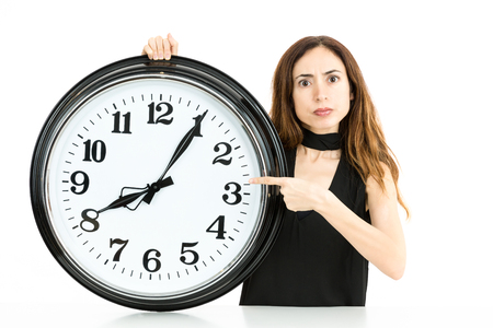 woman with clock: Woman pointing to clock Stock Photo