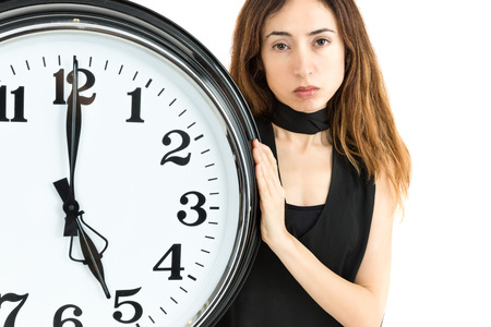 tiredness: Woman showing clock with a tired expression Stock Photo