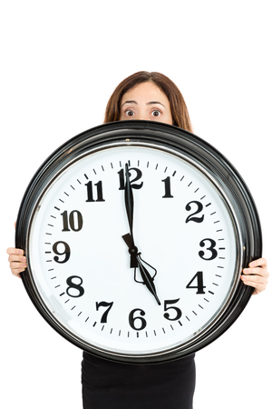 panicked: Woman late and showing the time with shocked eyes Stock Photo