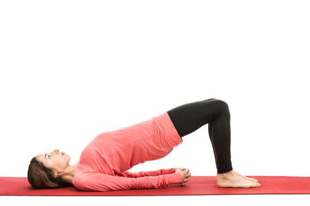 Caucasian woman doing bridge pose in yoga. Isolated on white background.