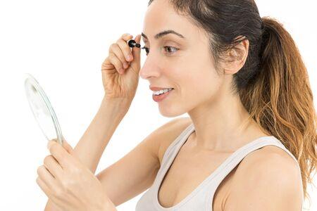woman mirror: Woman looking to mirror and applying mascara