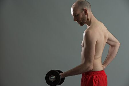 tricep: Caucasian handsome fitnes man training his arms with weights