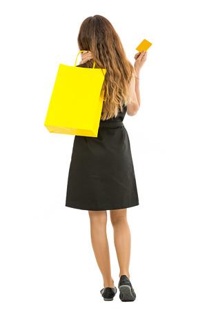 Winkelende vrouw die met een het winkelen zak en een creditcard in haar hand weggaat. Geïsoleerd op witte achtergrond