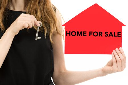 home sale: Woman hands showing a key and home for sale. Isolated on white background.