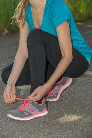 binding: Woman binding her sports shoes before jogging outdoors Stock Photo