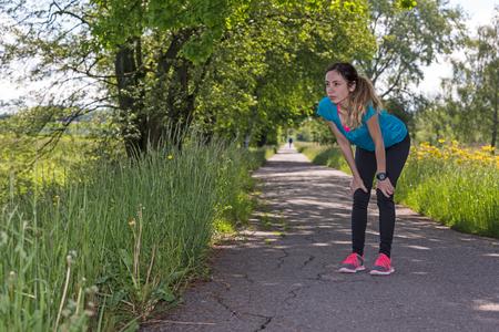 taking a break: Caucasian runner woman taking a break during exercise outdoors.