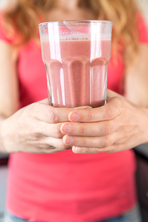 Close up of female hands holding a glass of smoothie