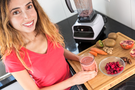 Smiling healthy nutrition woman drinking fresh made smoothie