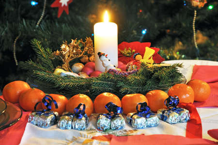 reed Christmas on the table and tangerines and candy photo