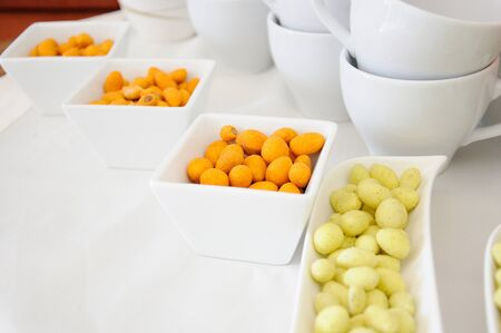 batter: peanuts with yellow and orange batter in white containers on the white table with cups Stock Photo