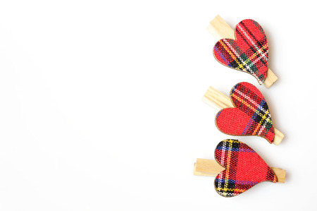 clasps: three hearts with red cloth, in plaid, with wooden clasps, next to each other on a white background
