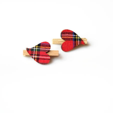 clasps: two hearts with red cloth, in plaid, with wooden clasps, opposite each other on a white background Stock Photo