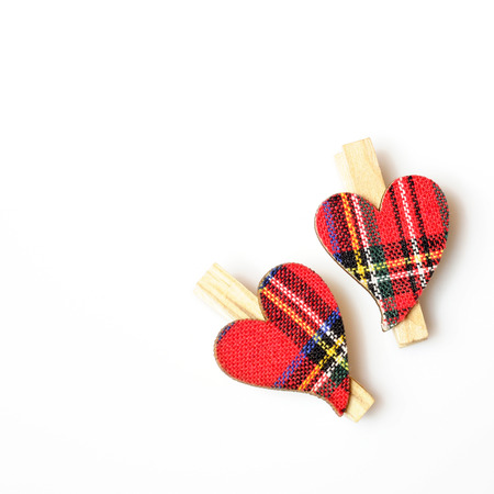 next to each other: two hearts with red cloth, in plaid, with wooden clasps, next to each other on a white background, in right corner