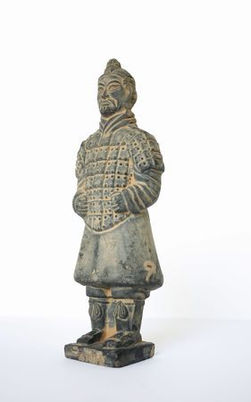 Side view of a standing terracotta worrier foot solider against a white background