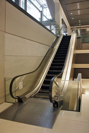 conveyor rail: Escalator beside a stone wall leading to the lobby in a modern building