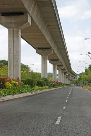 Elevated light rail tracks running along an empty road