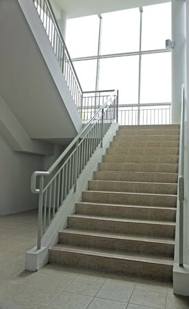 Treppenhaus mit breiten Treppe und voller Länge Glasfenster führt in den Keller Standard-Bild
