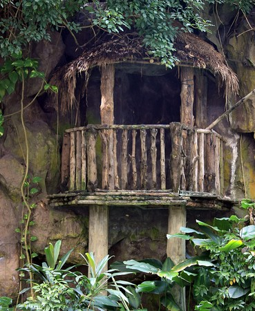 Ancient wooden hut balcony built against a rock wall Stock Photo