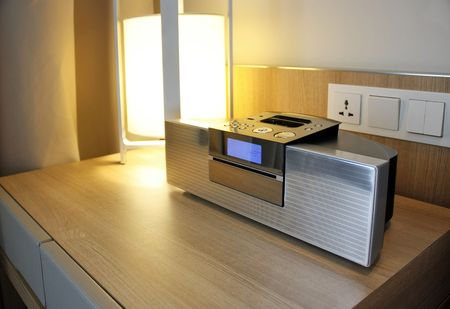 Digital radio with dock on a side table next to a lamp photo