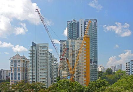 2 cranes at a condominium construction site.