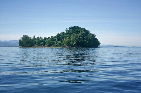 Kleine boom behandeld eiland met een strook strand in het midden van de blauwe zee