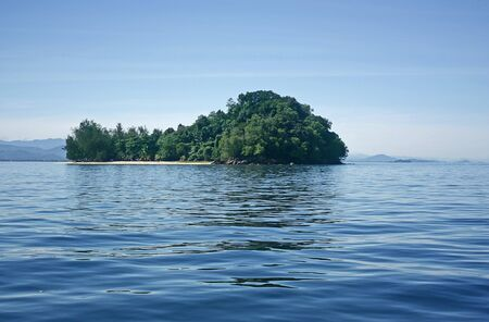 Small tree covered island with a strip of beach in the middle of the blue sea