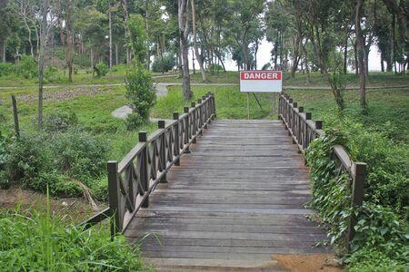 Houten brug over een stroom met een waarschuwing voor gevaar Stockfoto