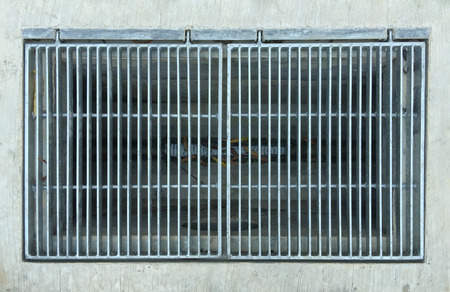 Storm drain metal grill on pavement