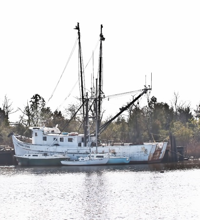 GEORGETOWN, SC - JANUARY 2012 - Sailboats are moored against a large shrimp boat in Georgetown Harbor, South Carolina