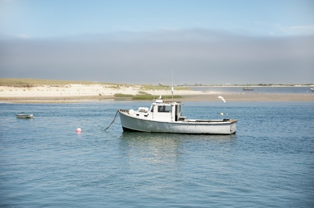lobster boat: A lobster boat anchored in a quiet bay in Chatham, MA Stock Photo