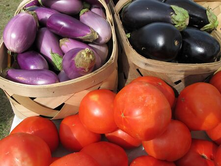 brighten: Baskets of bright red tomatoes and purple eggplant brighten a farmers market. Stock Photo