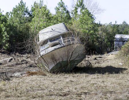 A pleasure boat lies abandoned in an open field near Conway, SC Reklamní fotografie - 19683735