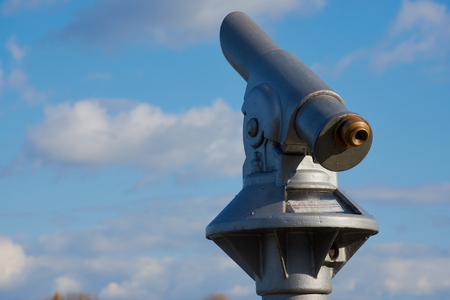 Public telescope against blue cloudy sky