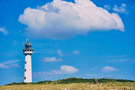Egmond aan Zee lighthouse, North Holland on a sunny day with a big white cloud over Stockfoto
