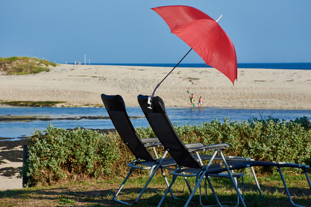 Two sun loungers and a red parasol in front of the lagoon of Benodet